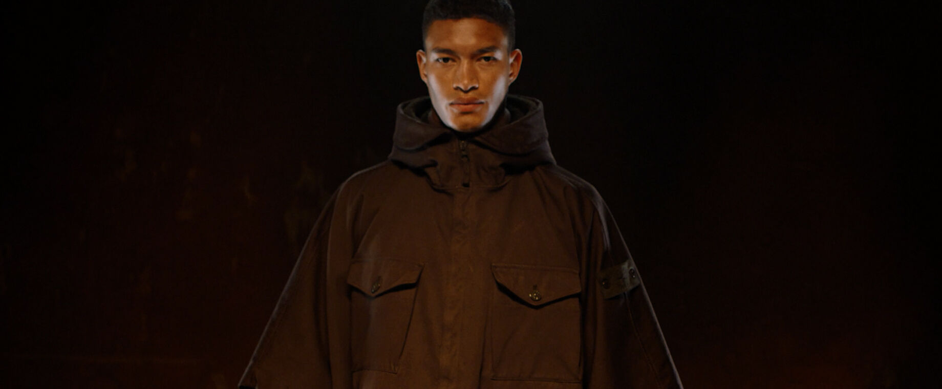 Close up shot of model wearing dark brown hooded jacket with hidden zipper closure, two bellows chest pockets with flap and button fastening and the Stone Island ghost badge on upper left arm.