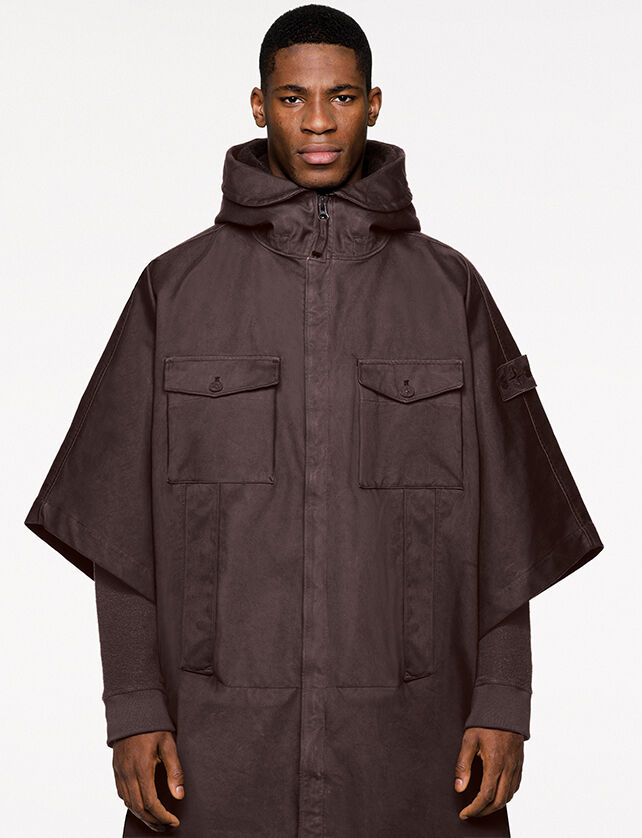 Model wearing dark brown hooded cape with hidden zipper closure, two bellows chest pockets with flap and button fastening, hand pockets and the Stone Island ghost badge on upper left arm.
