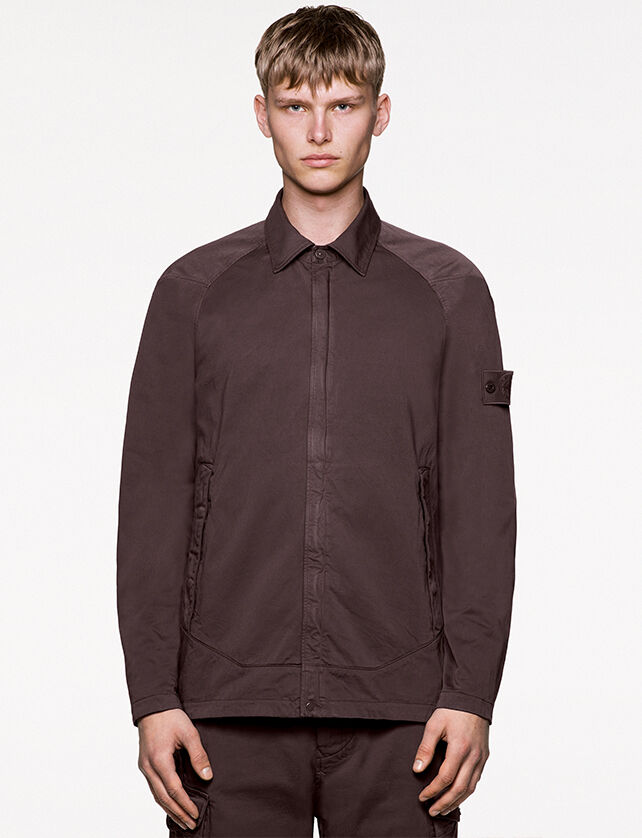 Model wearing dark brown pants and a matching bomber jacket with two hand pockets, ribbed collar, cuffs and bottom band.