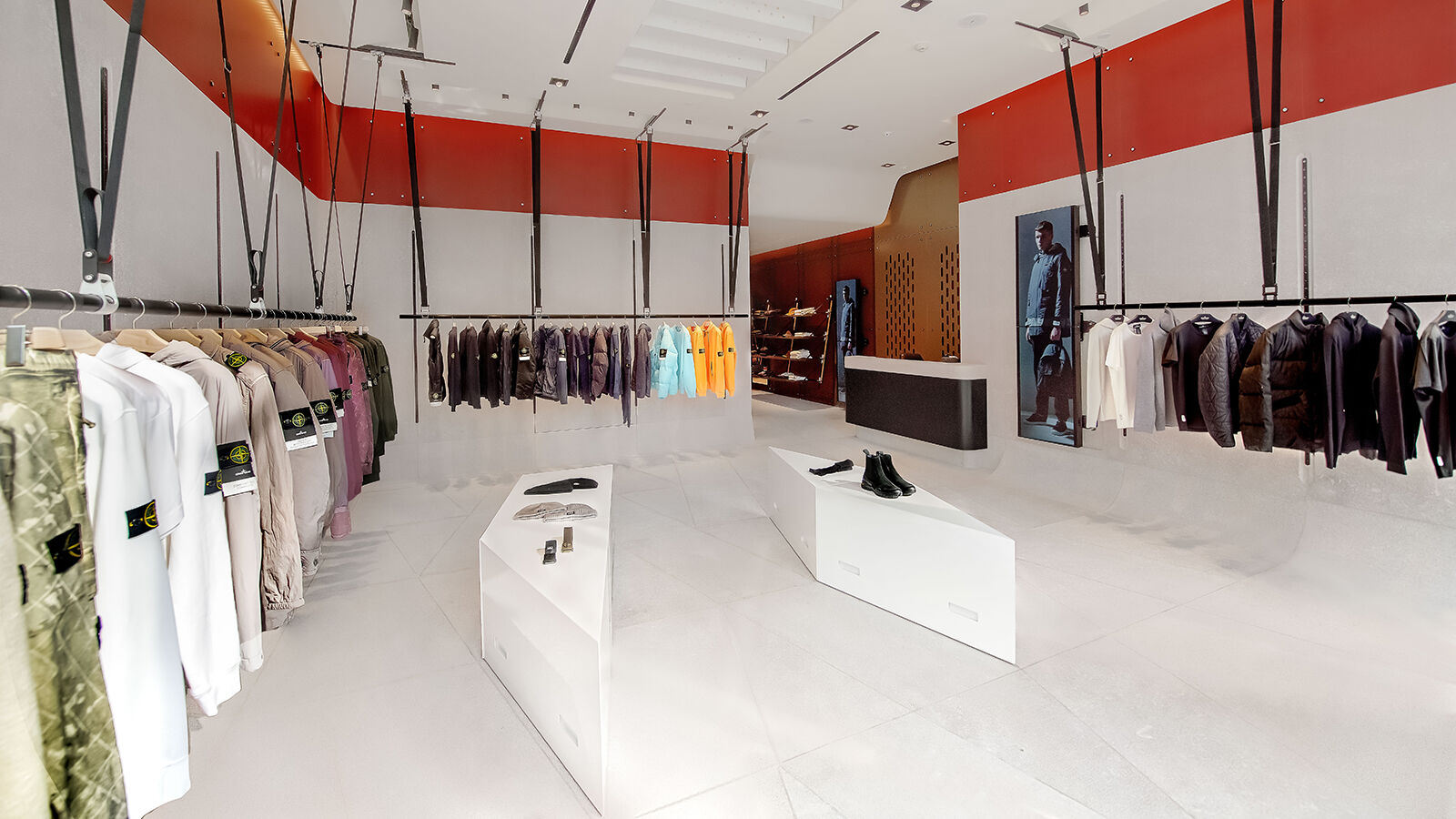 Interior view of a store with red accents, garments arranged by color hanging on racks along the side walls and two white display tables with shoes and accessories in the center.