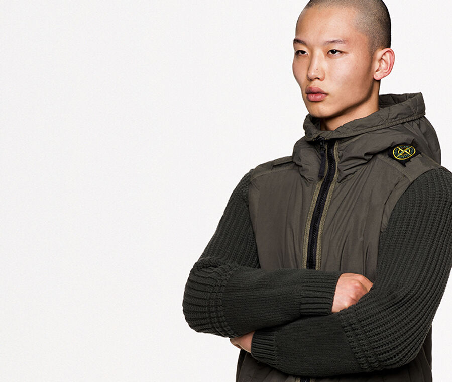 Model wearing a military green jacket with knit sleeves, standing collar, black zipper fastening, two slanting hand pockets and the Stone Island badge on the left shoulder.