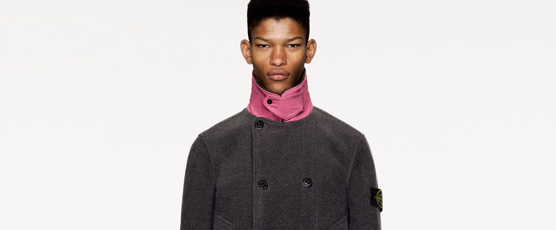 Model wearing dark colored pants and a dark gray pea coat with pink standing collar, chin strap held by button fastening, double breasted buttoning, two patch pockets and pink parallel stripes on the cuffs and lower hem.