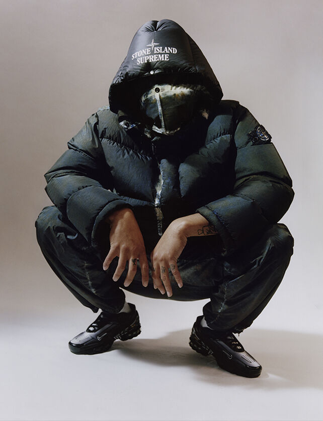 One crouching model wearing dark colored cargo pants with white edged patch bellows pocket on the left thigh and a matching down jacket with face flap and a hood with the Stone Island Supreme logo.