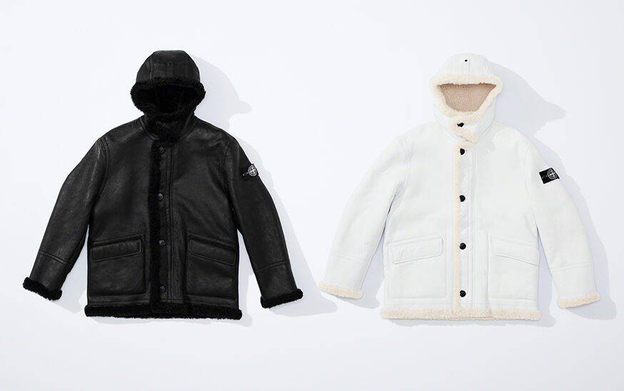 Still life image of two hooded sheepskin jackets, one black, one white, with button fastening, two slanting patch hand pockets with flap and the Stone Island research badge on the upper left arm.
