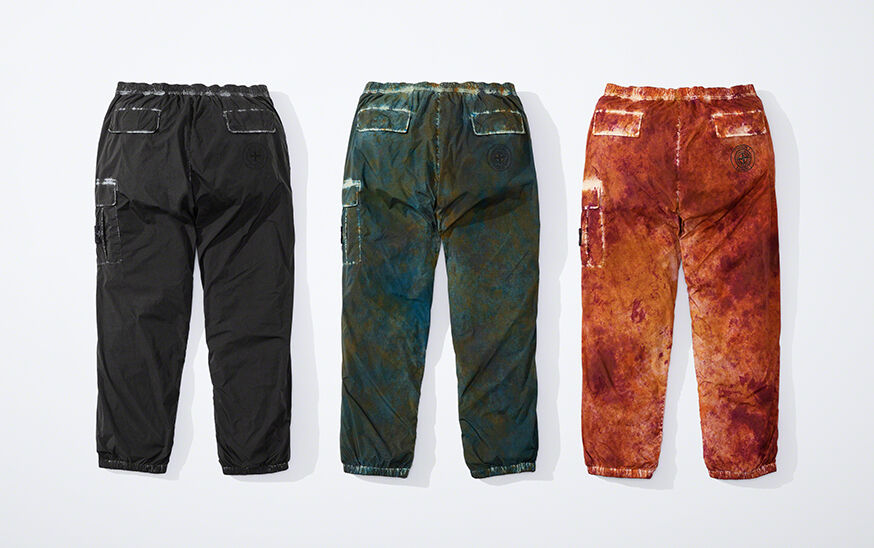 Still life image showing the back of three cargo pants, one black, one dark green camouflage and one orange camouflage, all with elasticated waist and leg bottoms, two back pockets with flap and a patch pocket with flap on the left thigh.