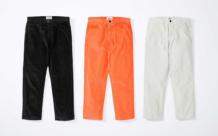 Still life image of three straight pants, one black, one bright orange and one off white, showing a waist with belt loops and drawstring, zip and button fly and a five pockets design.