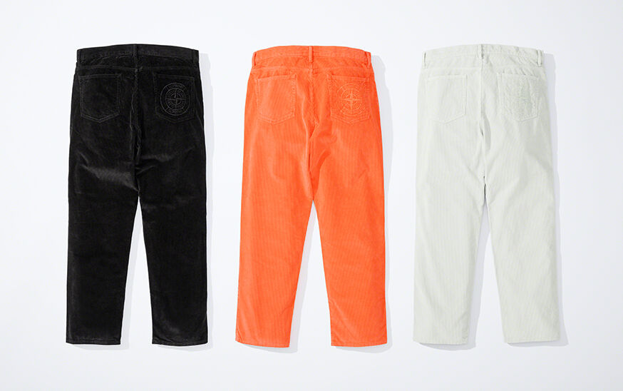 Still life image showing the back of three straight pants, one black, one bright orange and one off white, showing a waist with belt loops and two back patch pockets with a matching Supreme Stone Island logo on the right one.