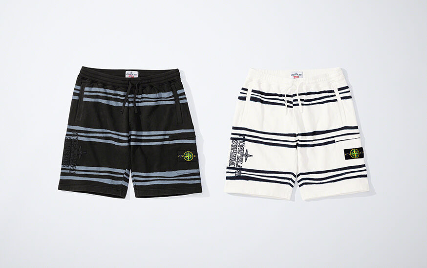 Still life image of two short pants, one black with blue gray stripes and one white with black stripes, both showing an elasticated waist with drawstring, welt hand pockets, the Stone Island Supreme logo on the right thigh and the Stone Island badge on th