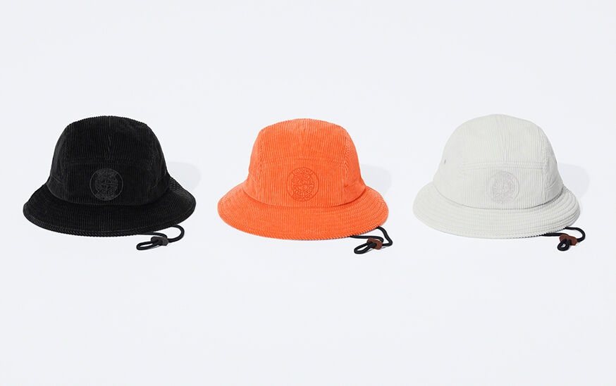 Still life image of three corduroy bucket hats, one black, one bright orange and one white, all showing a matching compass rose that reads Supreme Stone Island and a dark colored adjustable neck cord.