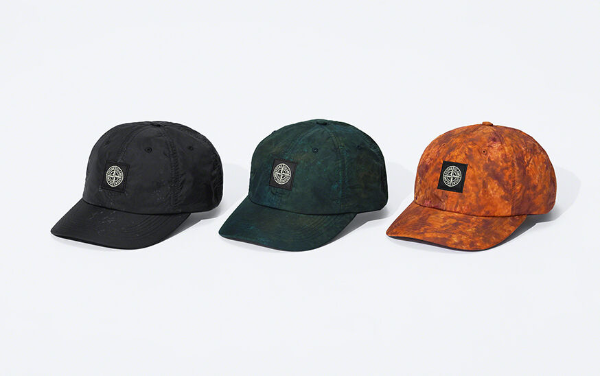 Still life image of three caps, one black, one dark green camouflage and one orange camouflage, all showing a visor and the Stone Island Compass logo patch.