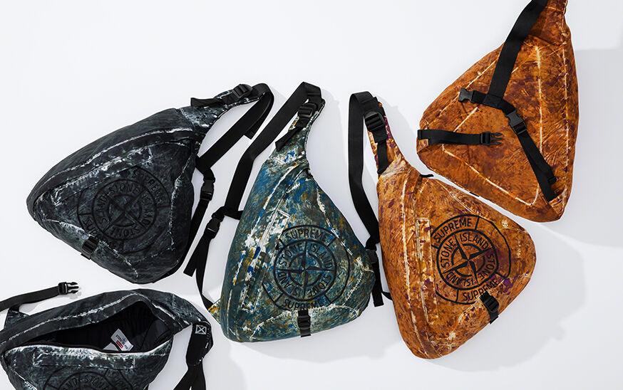 Still life image of triangle shaped bags with adjustable straps, two black camouflage, one dark green camouflage and two orange camouflage, with a dark colored compass rose that reads Supreme Stone Island.