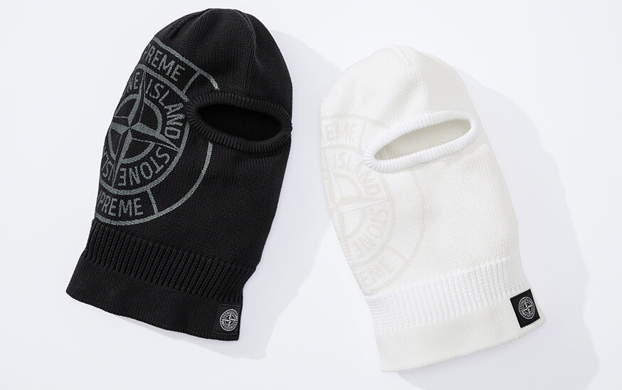 Still life image of two knit balaclavas, one black, one white, both with ribbed details, the Stone Island Compass logo patch on the bottom hem and a large compass rose that reads Supreme Stone Island on the right side.