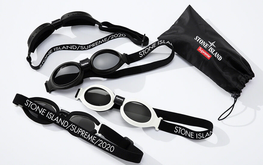 Still life image of a glasses soft case with drawstring and both the Stone Island and Supreme logos, goggles with dark lenses, two black and two white, all with a band that reads STONE ISLAND/SUPREME/2020.