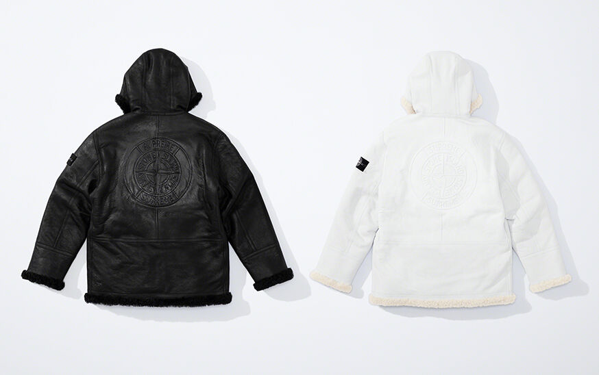 Still life image showing the back of two hooded sheepskin jackets, one black, one white, each with a matching compass rose that reads Supreme Stone Island and the research badge on the upper left arm.