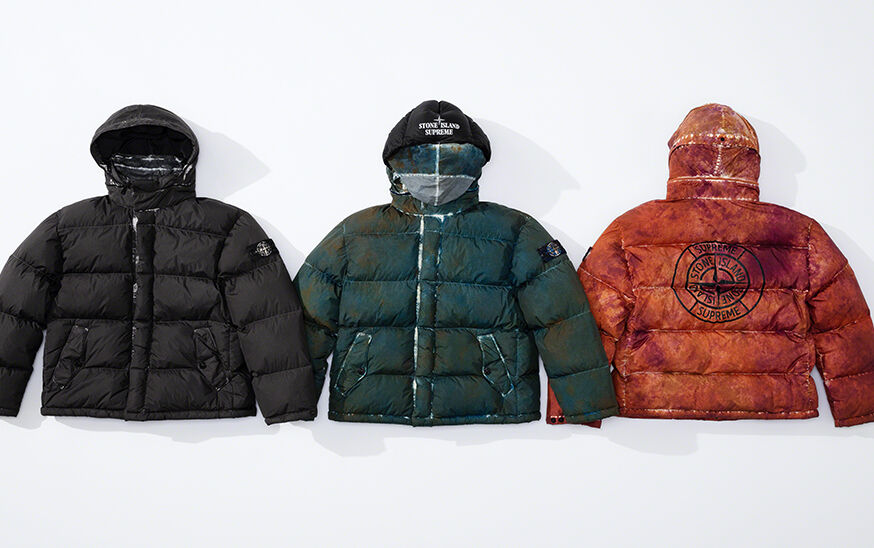 Still life image of three hooded down jackets, one black, one dark green with Stone Island Supreme logo on hood and one orange showing a compass rose that reads Supreme Stone Island on the back.