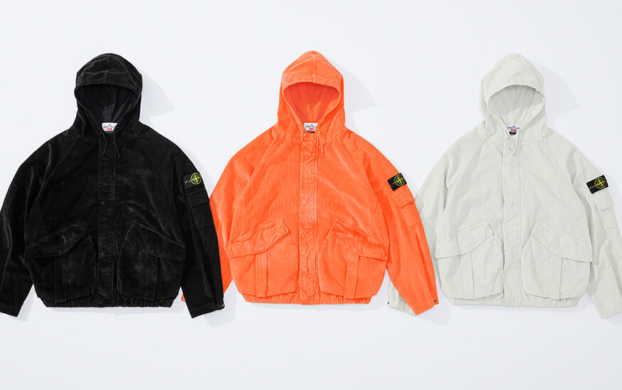 Still life image of three hooded jackets, one black, one bright orange and one off white, with elasticized bottom hem, two slanting patch hand pockets with pleat and flap and the Stone Island badge on the upper left arm.