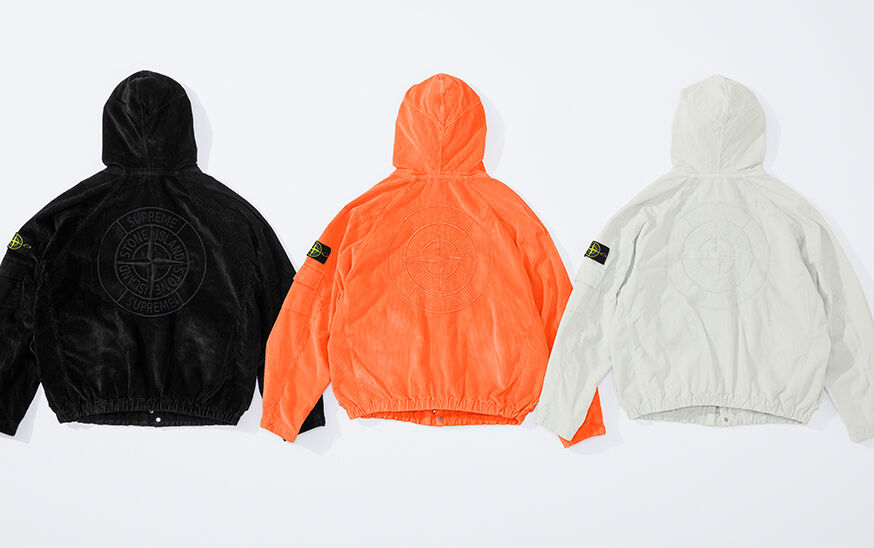 Still life image showing the back of three hooded jackets, one black, one bright orange and one off white, each with a matching compass rose that reads Supreme Stone Island and an elasticized bottom hem.