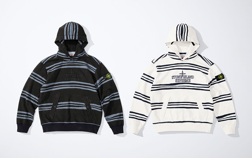 Still life image of two hooded sweatshirts, one black with blue gray stripes and one white with black stripes, both showing a pouch pocket with slanting side entrances held by buttons and the Stone Island Supreme logo on the chest.