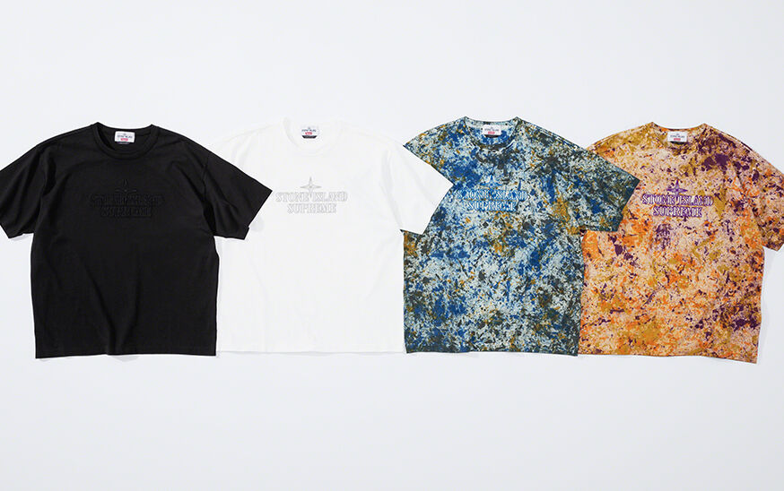 Still life image of four crewneck t shirts, one black, one white, one with a blue and green print and one with an orange and purple print, all with the Stone Island Supreme logo on the chest.