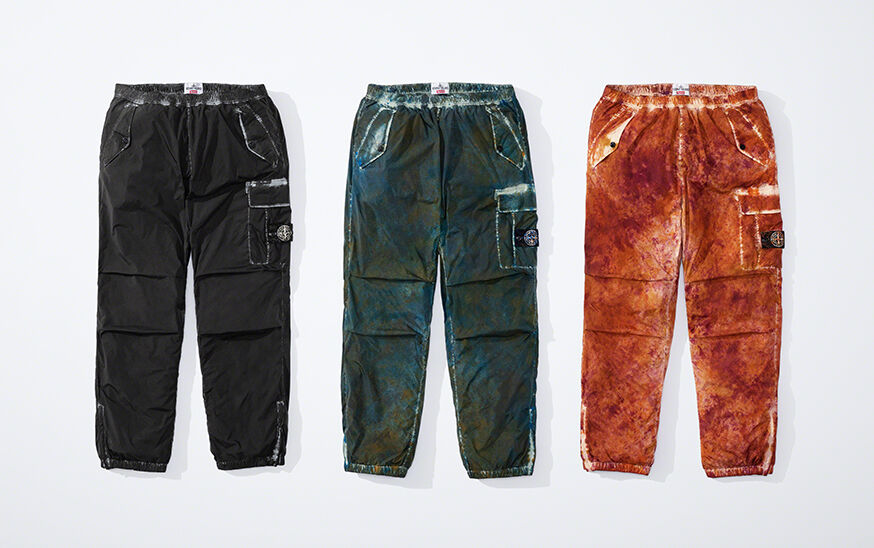 Still life image of three cargo pants, one black, one dark green camouflage and one orange camouflage, all with elasticated waist and leg bottoms, slanting hand pockets with flap and button and a patch pocket with flap and the Stone Island research badge