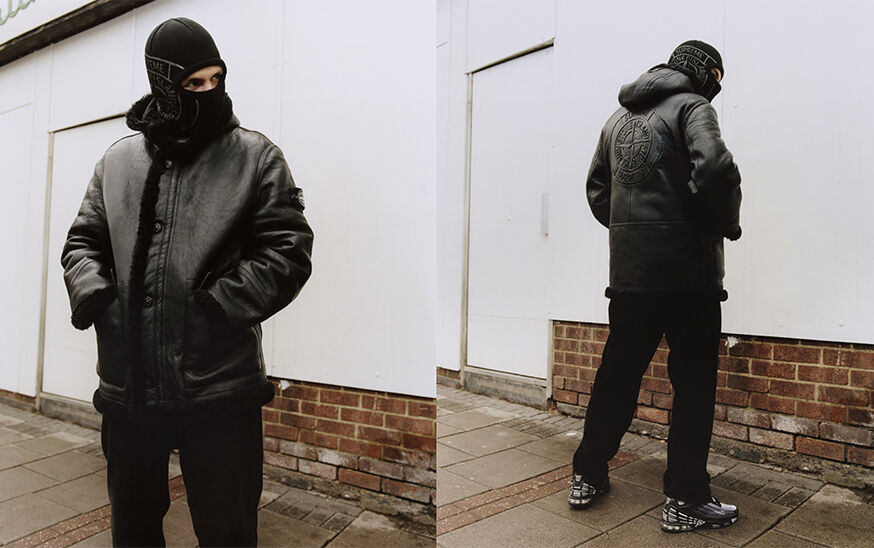 Two shots of the same model, showing the front and back, wearing black pants, a black hooded sheepskin jacket with the Supreme Stone Island logo on the back and a black balaclava with a large gray Supreme Stone Island logo on the side.