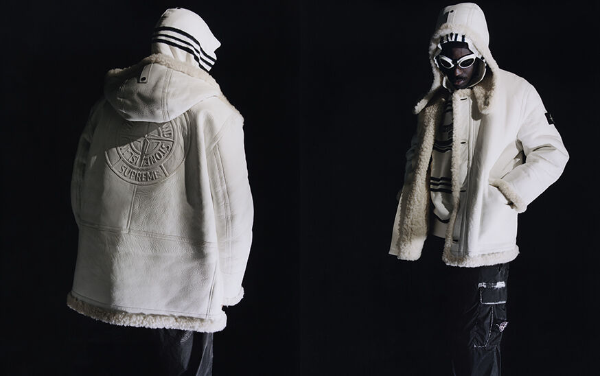 Two shots of the same model, showing the front and back, wearing black cargo pants with white edged patch bellows pocket on the left thigh, a white hooded sheepskin jacket, a black and white striped hoodie and white goggles with dark lenses.