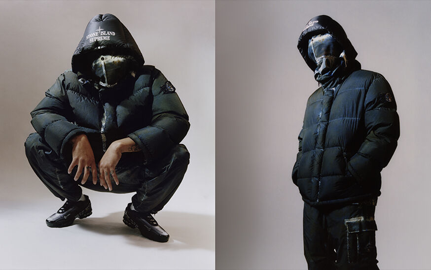 Two shots, one crouching down and one standing, of the same model wearing dark colored cargo pants with white edged patch bellows pocket on the left thigh and a matching down jacket with face flap and a hood with the Stone Island Supreme logo.