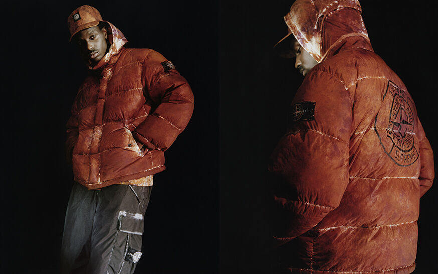 Two shots of the same model, showing the front and back, wearing dark colored cargo pants with white edged patch pocket on the left thigh, an orange camouflage down jacket with hood and a matching cap with the Stone Island Compass logo patch.