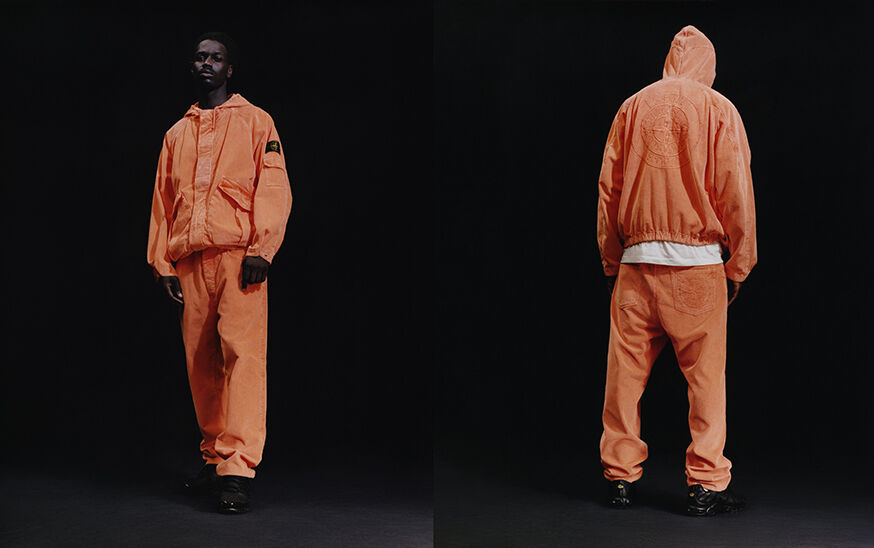 Two shots of the same model, showing the front and back, wearing black sneakers, orange baggy pants with a matching hooded jacket with elasticized bottom hem, two slanting patch hand pockets with pleat and flap and the Stone Island badge on the upper left