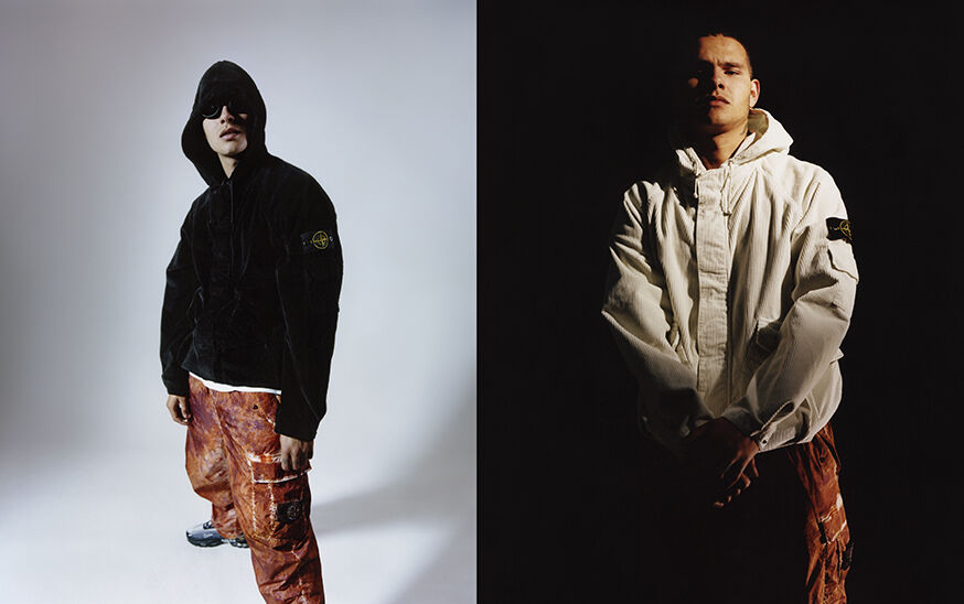 Two shots, one with a model wearing orange camouflage cargo pants and a black hooded jacket, the other one of a model wearing orange camouflage cargo pants and an off white hooded jacket with the Stone Island badge on the upper left arm.