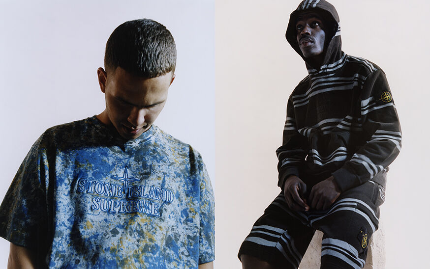 Two shots, one with a model wearing a blue and green camouflage crewneck t shirt, the other one of a model wearing a black hooded sweatshirt with irregular blue gray stripes and matching shorts with the Stone Island badge on the left thigh.
