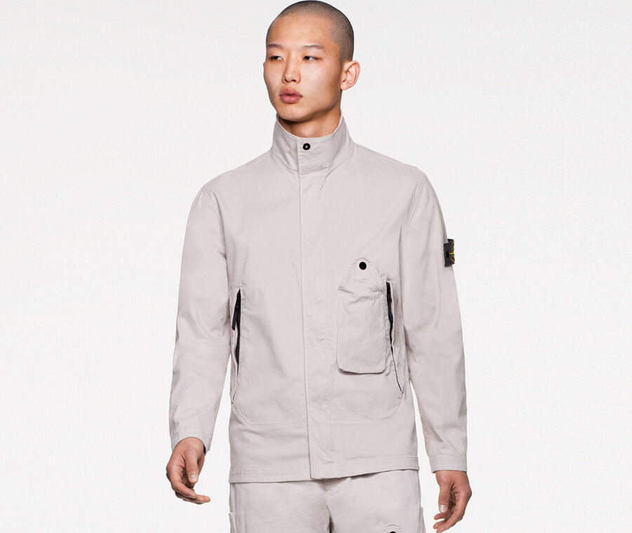 Model wearing off white pants and a matching overshirt featuring a standing collar with small button fastening, slanting hand pockets with zipper and one front bellows patch pocket with a standing triangular flap fastened by a snap.