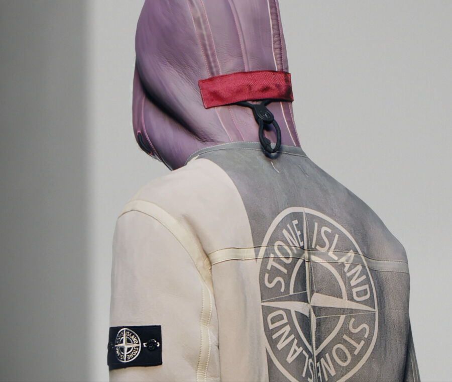 Close up shot of model seen from the back, wearing a gray, off white and purple suede sheepskin jacket with the Stone Island logo printed on the back and a hood featuring parallel vertical drawstrings with black toggle and pull.