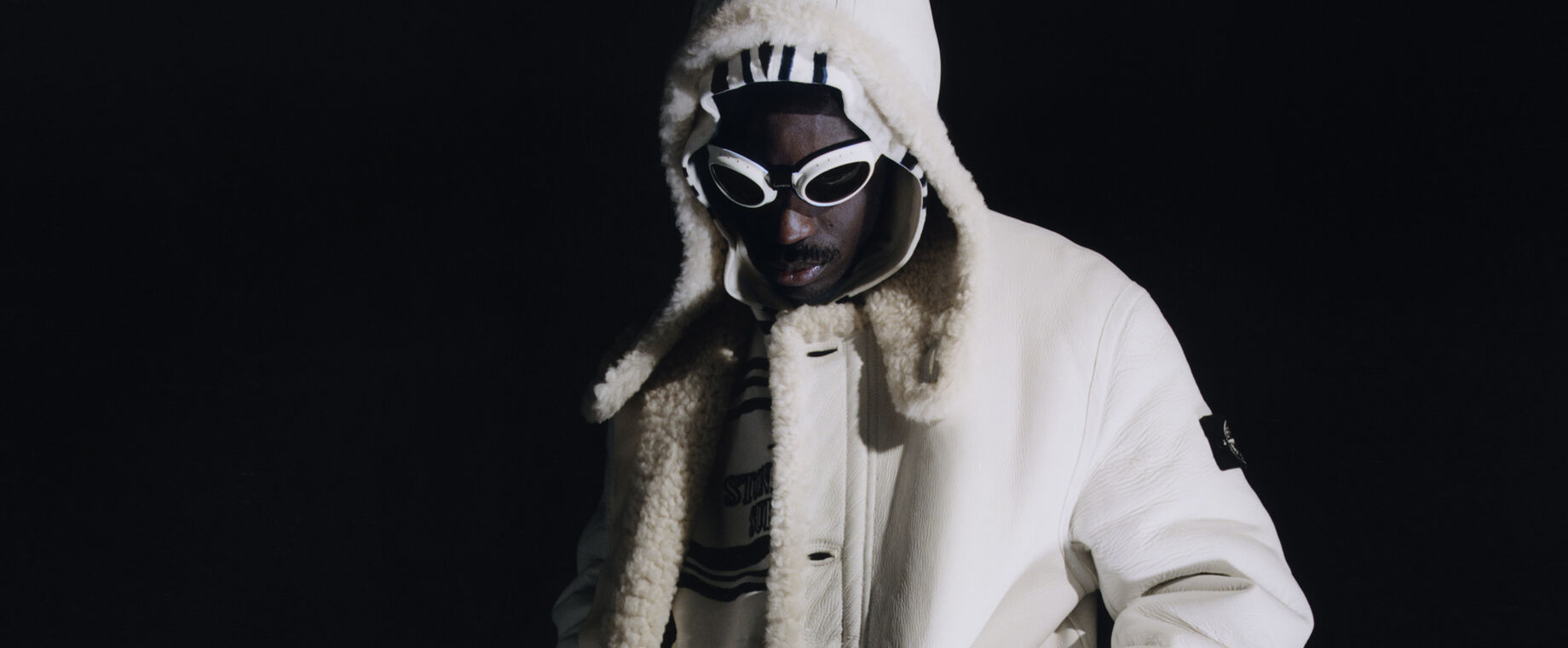 Against a black background, model wearing a white hooded sheepskin jacket, a black and white striped hoodie and white goggles with dark lenses.
