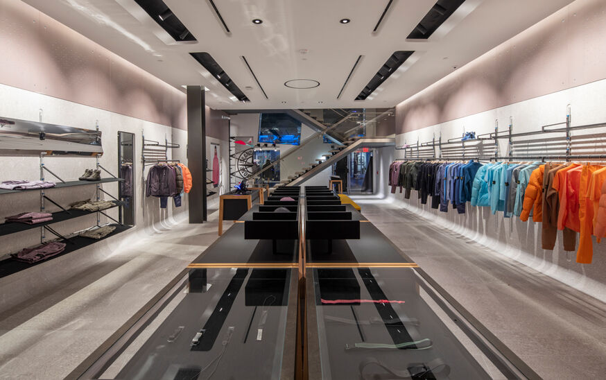 Interior view of a store with off white walls, floor and ceiling, garments arranged by color hanging on a rack on the right, a display table with accessories in the center and on the left racks with a pair of shoes, garments both hanging and folded.