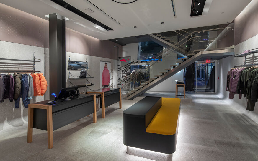 Interior view of a store with a metal and glass staircase at the back, showing the cash register and garments hanging on a rack on the left, a black and yellow sofa in the center and garments arranged by color hanging on a rack on the right wall.