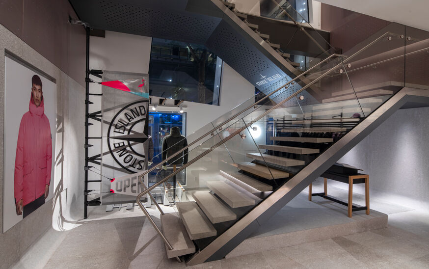 Interior view of a store with a metal and glass staircase on the right, a Stone Island compass rose logo banner and a big picture of a model wearing a pink parka on the left.