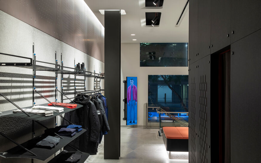 Interior view of a store with racks with shoes and garments both hanging and folded on the left, a black pillar, a rectangular screen showing a model with a bright colored jacket at the back and a black wall on the right.