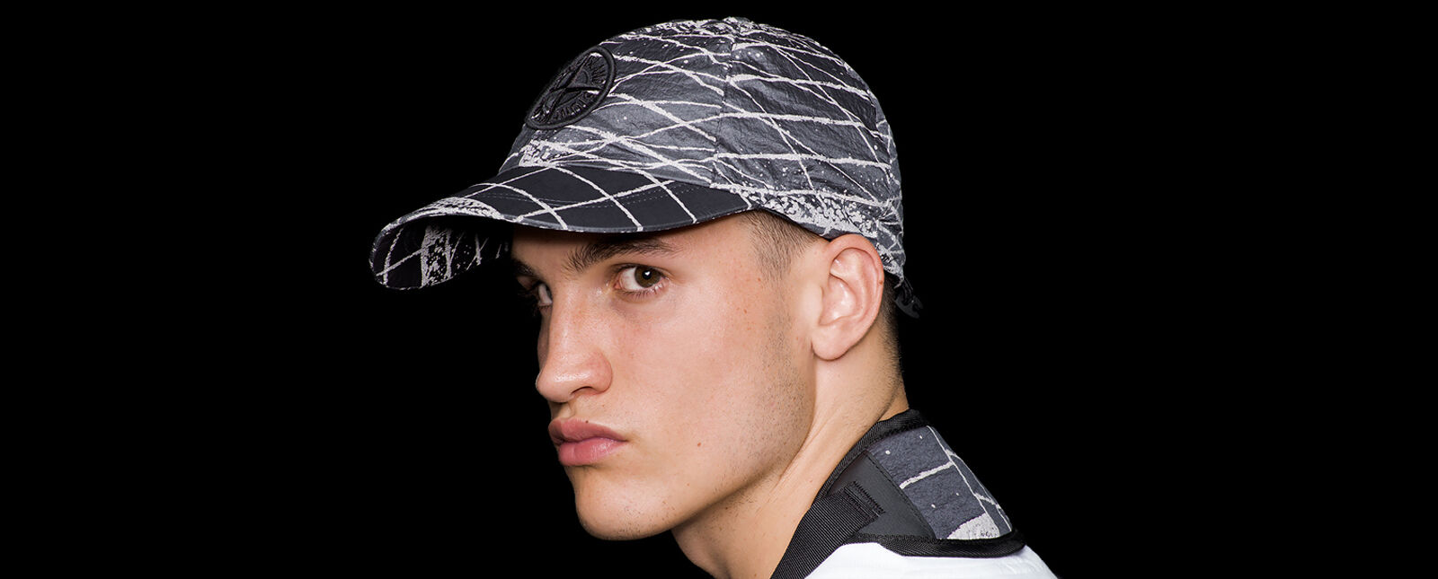 Close up shot of model wearing a dark gray and white print cap with the Stone Island Compass logo embroidery on the front and an elasticated drawstring on the back.