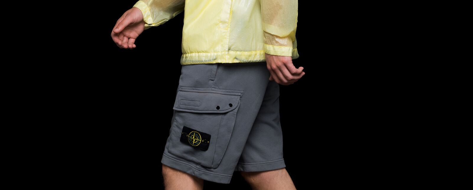 Close up shot of model wearing gray cargo shorts with the Stone Island badge on the left thigh and a yellow see through jacket with shiny effect and drawstring on the bottom band.