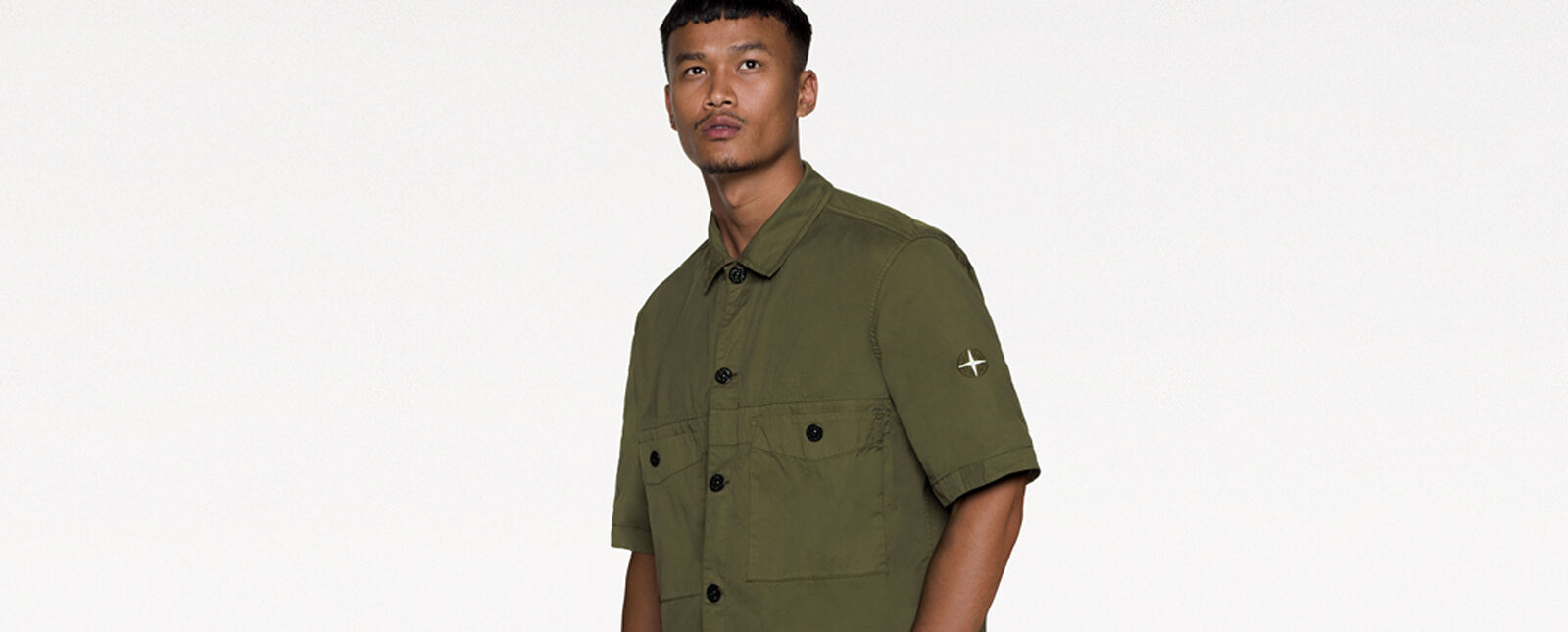 Model wearing a military green short sleeved shirt with button fastening, two patch pockets with snap fastening on the chest and the two tone Stone Island Compass logo embroidery on the left sleeve.