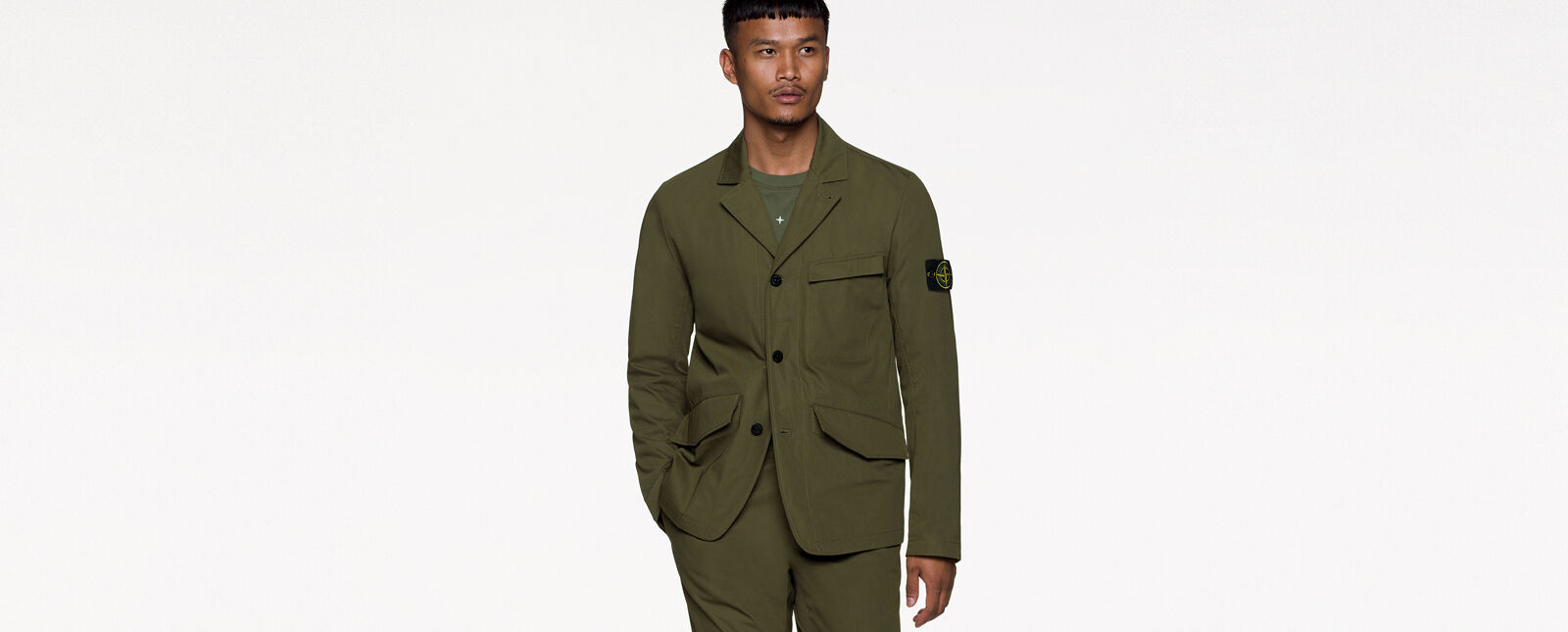 Model wearing military green pants and a matching jacket with collar, three button fastening, a chest pocket with flap, two hand pockets with slanting flap and the Stone Island badge on the upper left sleeve.