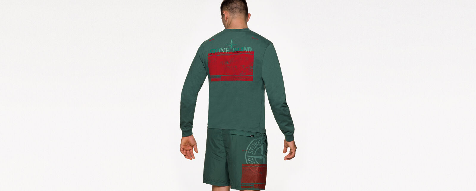 Back view of model wearing a green crewneck t shirt with long sleeves and a red print on the back and green shorts with a red print and the Stone Island compass rose logo on the right thigh.