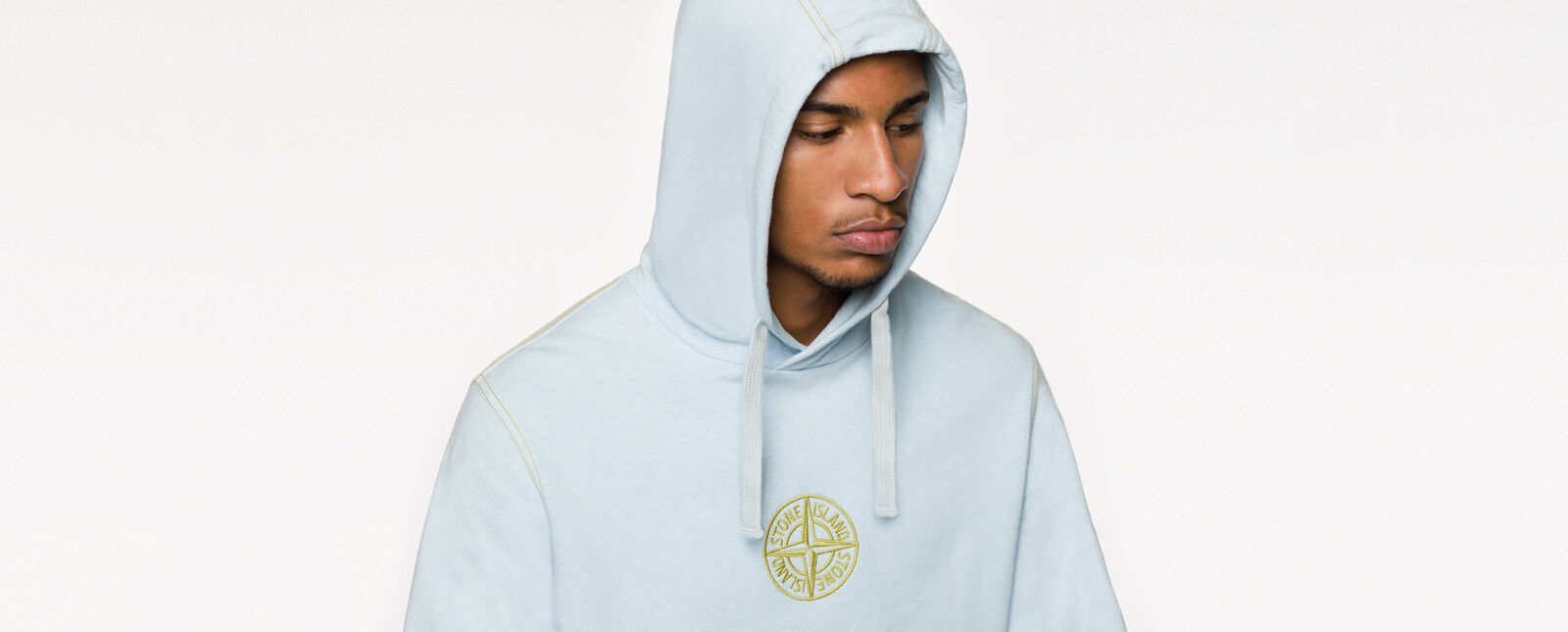Close up of model wearing a light blue sweatshirt with hood, yellow stitching and the Stone Island compass rose logo embroidered in yellow on the chest.