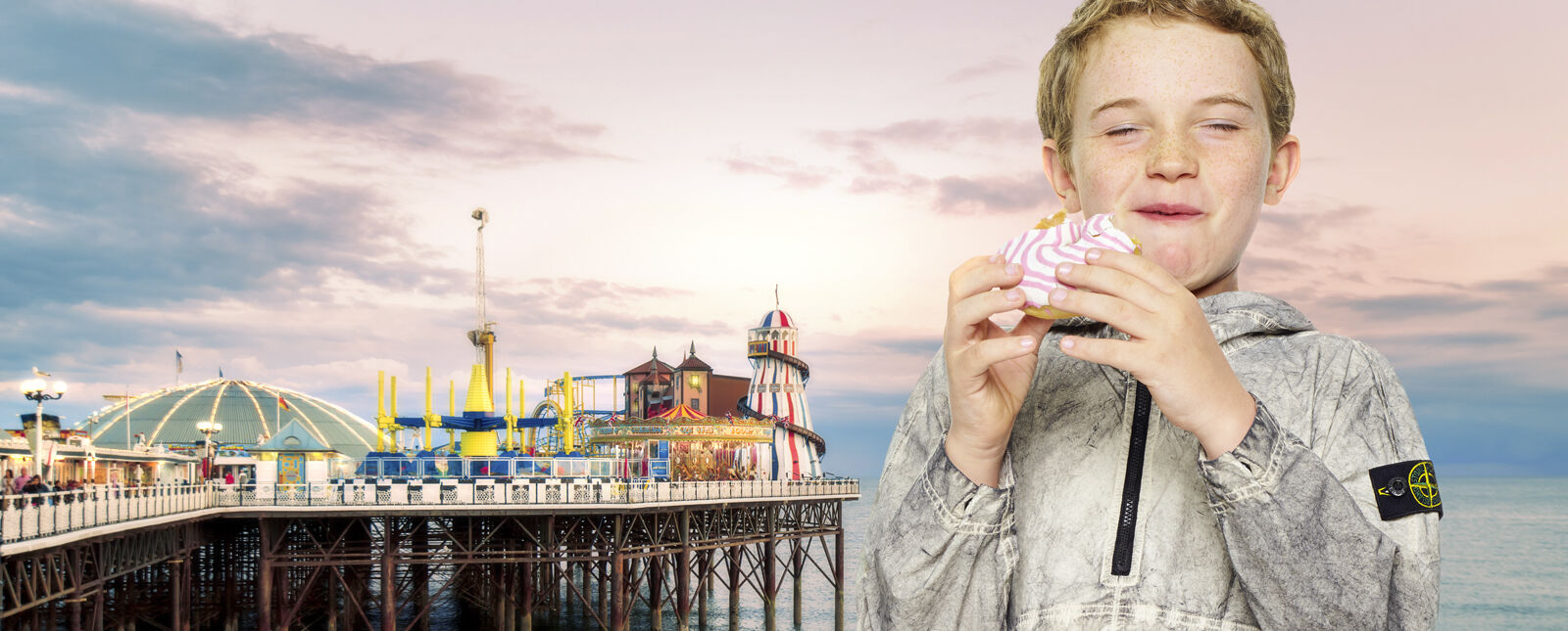 View of a pier amusement park and a waterfront promenade on the left and a close up shot of a junior model eating a donut, wearing an off white dust effect hooded jacket with half zipper and the Stone Island badge on the upper left arm.