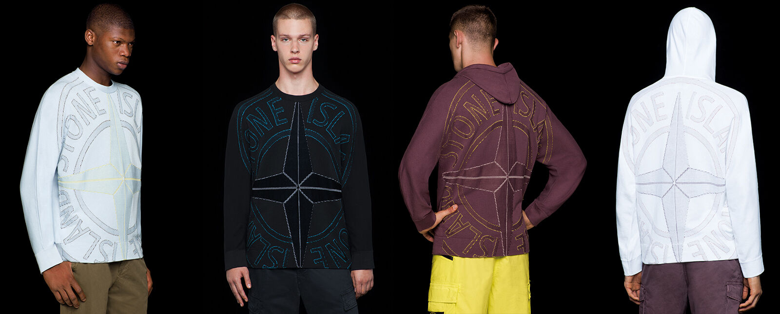 Four models wearing pants in different styles and colors, two of them wearing a crewneck t shirt with long sleeves and a large Stone Island compass rose logo embroidery on the front, the other two showing the same embroidery on the back of hooded sweatshi