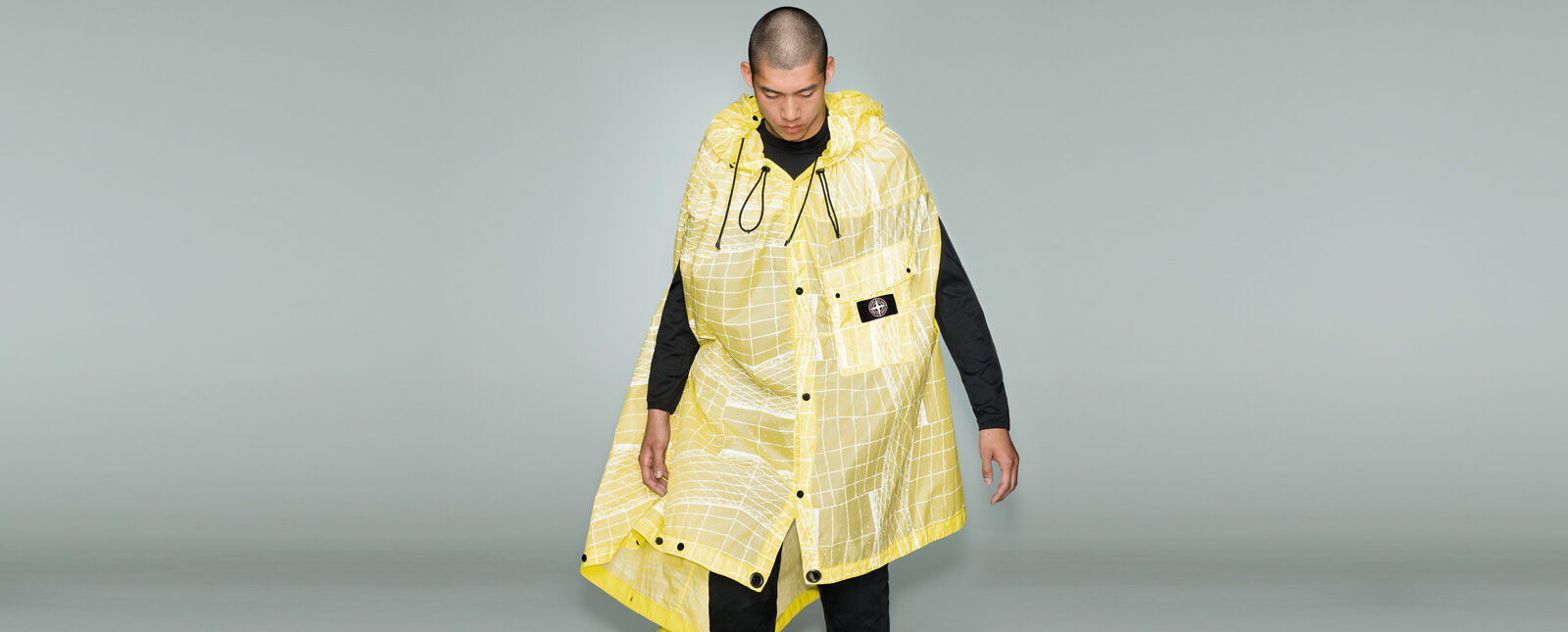 Model wearing black pants, a matching crewneck top and a yellow cape with a white print, a hood with drawstrings, button fastening and a patch pocket with flap, snaps and the Stone Island research badge.