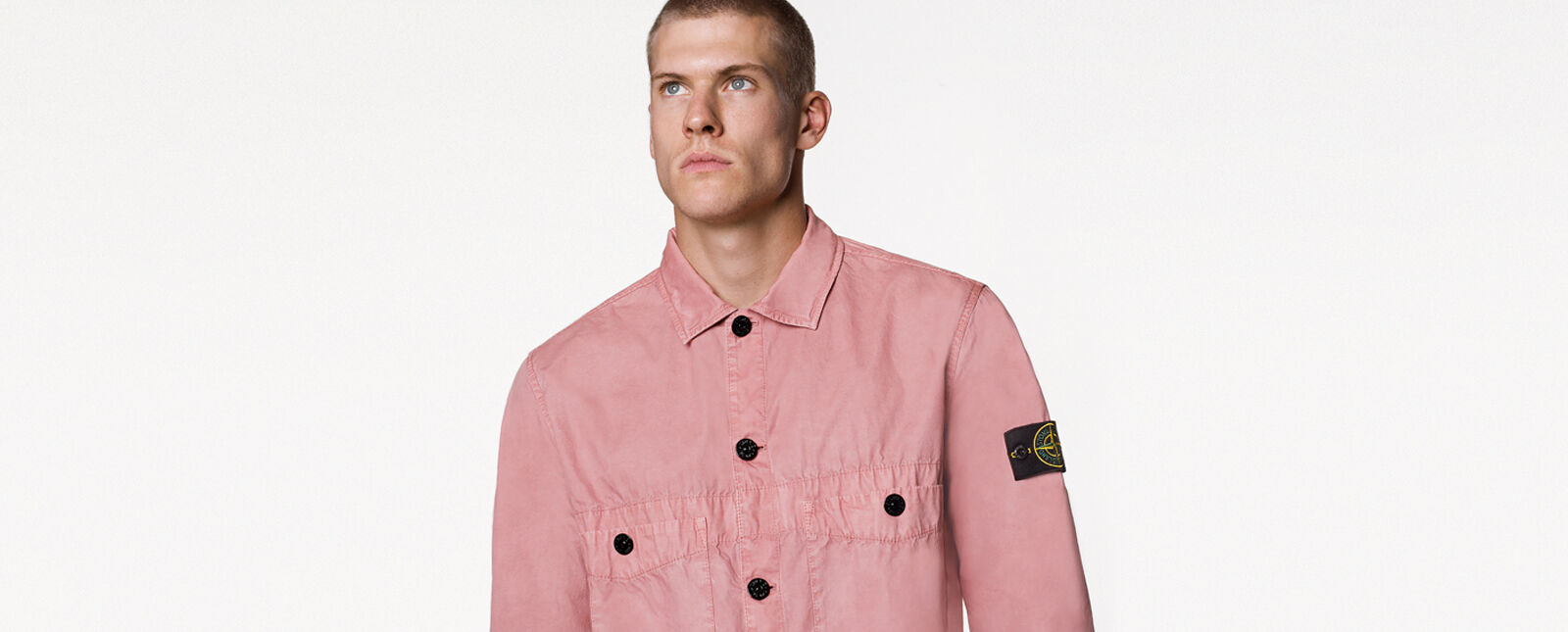 Close up shot of model wearing a light pink overshirt with collar, button fastening, two patch pockets with button fastening on the chest and the Stone Island badge on the upper left arm.