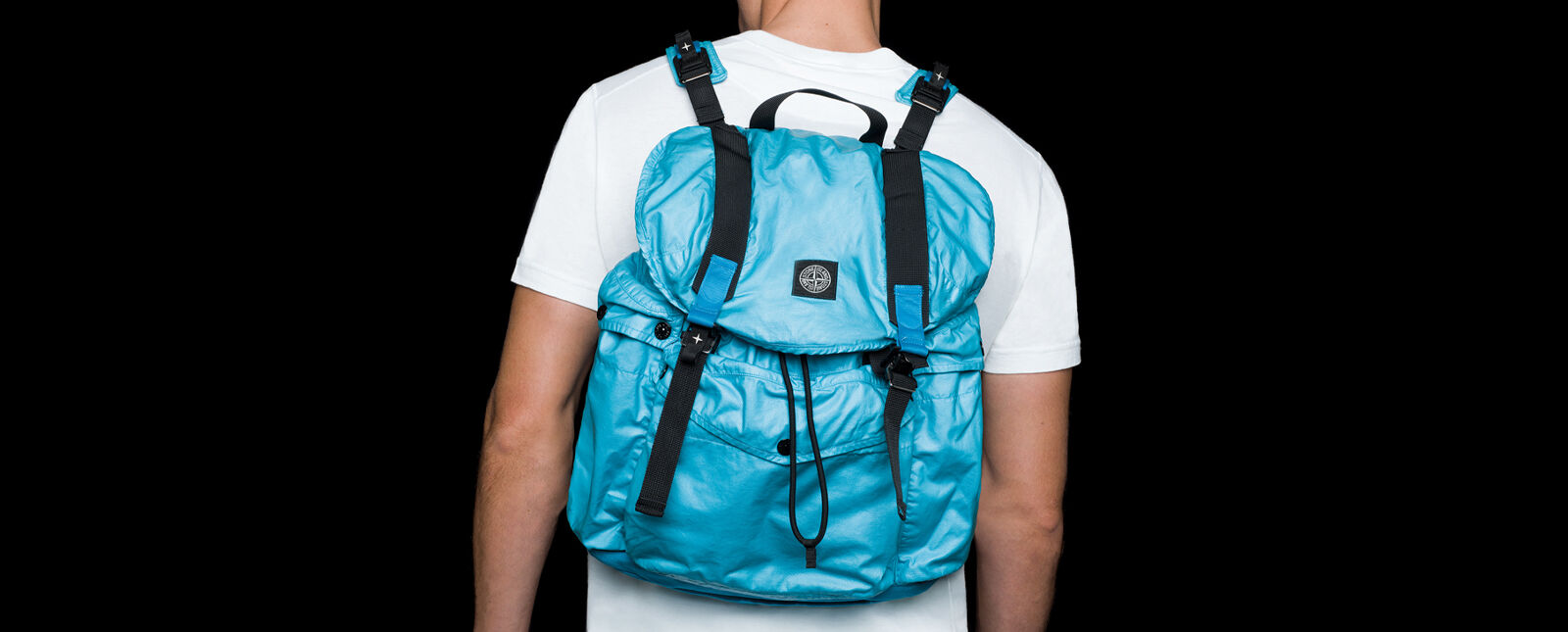 Back view of model wearing a white crewneck t shirt and a light blue shiny effect backpack with shoulder straps, flap cover with double fastening and a central pocket with flap and snap.