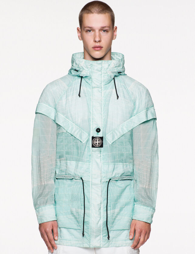Model wearing white pants and a light blue see through hooded jacket with a white print, drawstring at waist and a fastening placket with a buttoned central strap on the chest featuring the Stone Island research badge.
